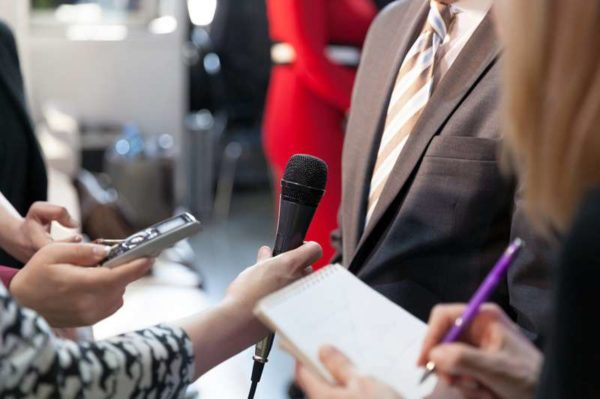 Reporter holding microphone conducting press interview