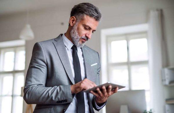 A waist-up portrait of mature businessman standing in an office, using tablet.